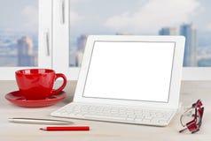 Tablet-PC mit Tastatur und rotem Becher auf Bürotisch Stockfotografie