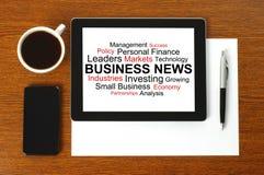 Tablet-PC mit Wirtschaftsnachrichten, intelligentem Telefon, Papier, Stift und Tasse Kaffee Stockfoto