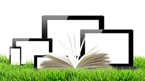 Tablet pc, mobile phone, computer and open book in green grass Royalty Free Stock Images