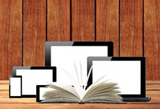Tablet pc, mobile phone, computer and openned book on wooden tab Stock Photography
