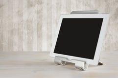 Tablet pc no suporte na tabela sobre a parede do grunge Imagem de Stock Royalty Free