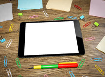 Tablet PC on the office table surrounded by multi- Royalty Free Stock Images