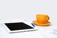 Tablet pc, orange cup and paper with graphs Stock Image