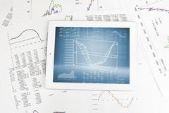 Tablet pc and paper with graphs Stock Image