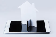 Tablet pc and paper house Stock Image