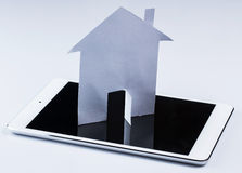 Tablet pc and paper house Stock Photos