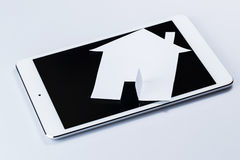 Tablet pc and paper house Royalty Free Stock Images
