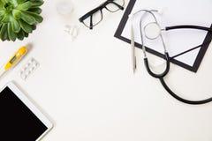 Tablet pc pelo termômetro e por instrumentos médicos no branco Fotos de Stock Royalty Free