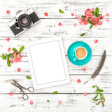 Tablet PC photo camera coffee pink flowers Spring flat lay Royalty Free Stock Image