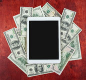 Tablet pc placed on center of money dollar and wood background, dark blank screen, business concept and information mockup Royalty Free Stock Photo
