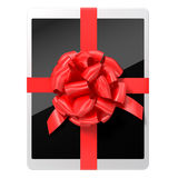 Tablet pc with a red ribbon on white background Royalty Free Stock Image