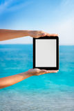 Tablet pc with  sea shore in background Royalty Free Stock Images