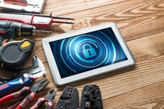 Web security and technology concept with tablet pc on wooden table. Tablet pc with security concept on screen and industrial tools around Royalty Free Stock Image