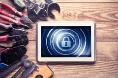 Web security and technology concept with tablet pc on wooden tab. Tablet pc with security concept on screen and industrial tools around Royalty Free Stock Photos