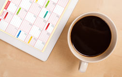 Tablet pc showing calendar on screen with a cup of coffee on a d Stock Photography
