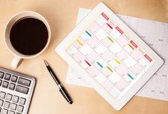 Tablet pc showing calendar on screen with a cup of coffee on a d Stock Photo
