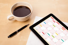 Tablet pc showing calendar on screen with a cup of coffee on a d Royalty Free Stock Image