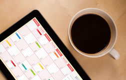 Tablet pc showing calendar on screen with a cup of coffee on a d Stock Images