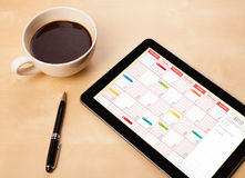 Tablet pc showing calendar on screen with a cup of coffee on a d Stock Image