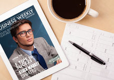 Tablet pc showing magazine on screen with a cup of coffee on a d Royalty Free Stock Image