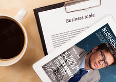 Tablet pc showing magazine on screen with a cup of coffee on a d Stock Image