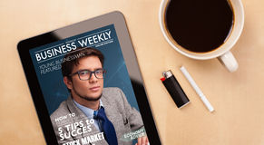 Tablet pc showing magazine on screen with a cup of coffee on a d Royalty Free Stock Images