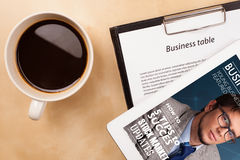 Tablet pc showing magazine on screen with a cup of coffee on a d Royalty Free Stock Photography