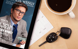 Tablet pc showing magazine on screen with a cup of coffee on a d Stock Photos
