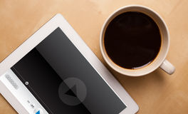 Tablet pc showing media player on screen with a cup of coffee on Stock Images