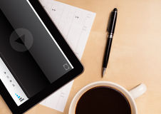 Tablet pc showing media player on screen with a cup of coffee on Royalty Free Stock Images