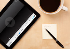 Tablet pc showing media player on screen with a cup of coffee on Royalty Free Stock Photos
