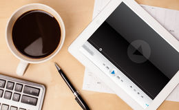 Tablet pc showing media player on screen with a cup of coffee on Royalty Free Stock Image