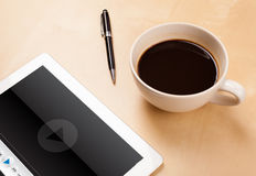 Tablet pc showing media player on screen with a cup of coffee on Royalty Free Stock Photo