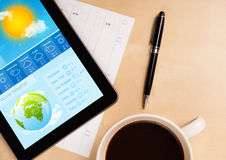 Tablet pc showing weather forecast on screen with a cup of coffe Royalty Free Stock Photos