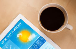 Tablet pc showing weather forecast on screen with a cup of coffe. Workplace with tablet pc showing weather forecast and a cup of coffee on a wooden work table Royalty Free Stock Photos