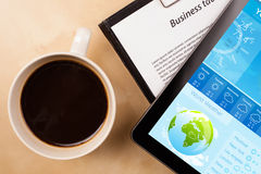 Tablet pc showing weather forecast on screen with a cup of coffe. Workplace with tablet pc showing weather forecast and a cup of coffee on a wooden work table Stock Image