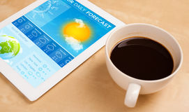 Tablet pc showing weather forecast on screen with a cup of coffe. Workplace with tablet pc showing weather forecast and a cup of coffee on a wooden work table Royalty Free Stock Images