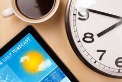 Tablet pc showing weather forecast on screen with a cup of coffe. Workplace with tablet pc showing weather forecast and a cup of coffee on a wooden work table Stock Photography