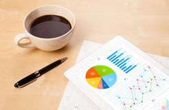 Tablet pc shows charts on screen with a cup of coffee on a desk Stock Photo