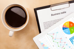 Tablet pc shows charts on screen with a cup of coffee on a desk Royalty Free Stock Image