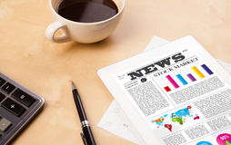 Tablet pc shows news on screen with a cup of coffee on a desk. Workplace with tablet pc showing latest news and a cup of coffee on a wooden work table close-up Stock Image