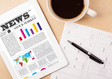 Tablet pc shows news on screen with a cup of coffee on a desk Royalty Free Stock Photography