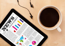 Tablet pc shows news on screen with a cup of coffee on a desk Stock Photography