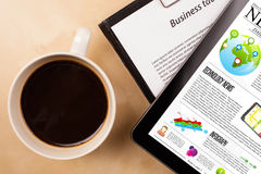 Tablet pc shows news on screen with a cup of coffee on a desk Stock Photo