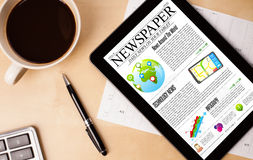 Tablet pc shows news on screen with a cup of coffee on a desk Stock Image