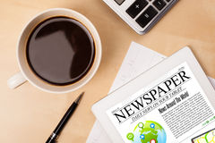 Tablet pc shows news on screen with a cup of coffee on a desk Royalty Free Stock Photo