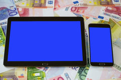 Tablet PC and Smart phone with blank touchscreen. Black Tablet PC and a black smart phone with blue blank touchscreen on a background of Euro banknotes Royalty Free Stock Images