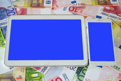 Tablet PC and Smart phone with blank touchscreen. White Tablet PC and a white smart phone with blue blank touchscreen on a background of Euro banknotes Stock Photo