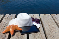 Tablet PC and straw hat at the swimming lake Royalty Free Stock Photography