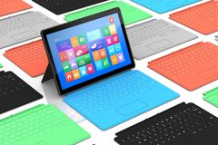 Tablet PC surrounded by keyboards. Tablet PC surrounded by colors keyboards Stock Photos